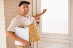Smiling handyman knocking at the door Royalty Free Stock Image