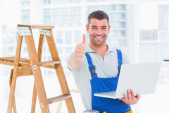 Smiling handyman with laptop gesturing thumbs up in office. Portrait of smiling handyman with laptop gesturing thumbs up in bright office Stock Photography