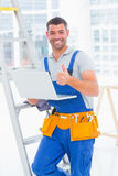 Smiling handyman with laptop gesturing thumbs up in office Stock Image
