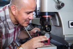 Smiling handyman making duplicates of door keys Royalty Free Stock Image