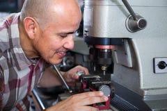 Smiling handyman making duplicates of door keys Stock Images