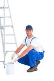 Smiling handyman in overalls opening paint can Royalty Free Stock Images
