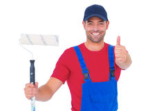 Smiling handyman with paint roller gesturing thumbs up Royalty Free Stock Photo