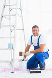 Smiling handyman with paintbrush and can at home Stock Photos