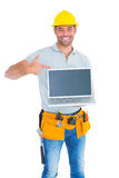 Smiling handyman pointing at laptop Stock Photography