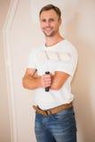 Smiling handyman posing while holding a paintbrush Stock Image