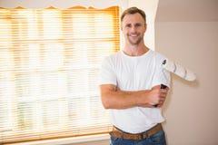 Smiling handyman posing while holding a paintbrush Stock Photography