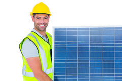 Smiling handyman in protective clothing carrying solar panel Royalty Free Stock Images