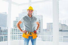Smiling handyman standing in building. Portrait of smiling handyman standing with hands on hips in building Royalty Free Stock Image
