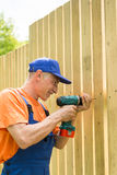Smiling handyman twirls a Royalty Free Stock Image