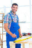 Smiling handyman using tape measure at workbench in office Royalty Free Stock Photography