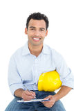 Smiling handyman with yellow hard hat writing in clipboard Royalty Free Stock Photos