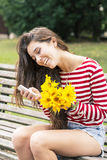 Smiling happiness woman with flowers looking message on mobile. Royalty Free Stock Photo