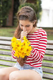 Smiling happiness woman with flowers looking message on mobile. Stock Image