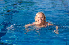 Smiling happy active elderly woman. Swimming a length of the pool doing breaststroke with a beaming smile in a healthy lifestyle and fitness concept royalty free stock images