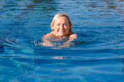 Smiling happy active elderly woman. Swimming a length of the pool doing breaststroke with a beaming smile in a healthy lifestyle and fitness concept stock image