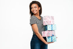Smiling happy african woman holding stack of present boxes. Portrait of a smiling happy african woman holding stack of present boxes and looking away at Royalty Free Stock Photos