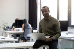 Smiling happy afro american businessman sitting on his desk. And holding laptop computer in an office Royalty Free Stock Image