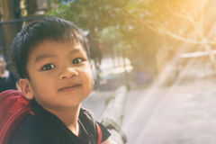 Smiling Happy Asian boy in morning sunshine. Royalty Free Stock Images