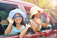 Smiling happy asian children waving hands on the car Stock Images