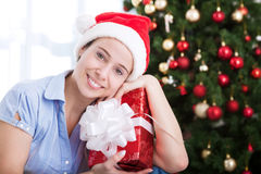 Smiling happy attractive girl holding christmas gift. At home Stock Photography
