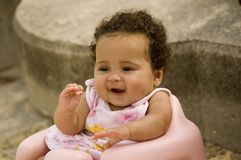 Smiling, happy baby. A smiling, happy baby sitting in a chair outdoors Stock Images