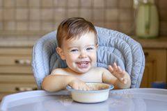 Smiling happy baby boy with eight teeth eating porridge wit his hands looking at camera sitting at high feeding chair at kitchen. First baby meal concept stock image