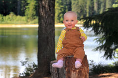 Smiling Happy Baby on Stump Stock Images