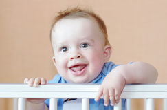 Smiling happy baby in white bed Stock Photography