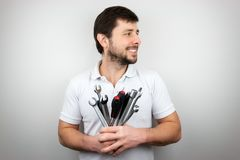A smiling happy bearded man with a bouquet of wrenches and screwdrivers looking to the side. A smiling happy bearded man in a white t-shirt with a bouquet of royalty free stock photo