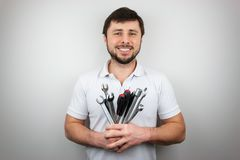 A smiling happy bearded man with a bouquet of wrenches and screwdrivers. A smiling happy bearded man in a white T-shirt with a bouquet of wrenches and royalty free stock image