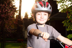 Smiling Happy Biker at Dusk. An happy smiling preteen boy at dusk with bike helmet on bike. Shallow depth of field Royalty Free Stock Image