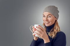 Smiling happy blond woman with a large mug of coffee. Smiling happy blond woman wearing a knitted winter hat and polo neck sweater standing indoors with a large royalty free stock images