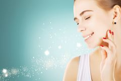smiling happy blond woman taking care of her skin,blue background stock image