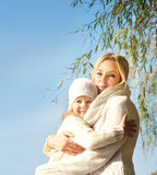 Smiling happy blonde woman and girl hugging outdoor in park against blue sky. Royalty Free Stock Photo