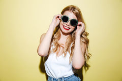 Smiling happy blonde woman wearing sunglasses and looking at camera. Portrait of a smiling happy blonde woman wearing sunglasses and looking at camera isolated Stock Image