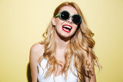 Smiling happy blonde woman wearing sunglasses. Portrait of a laughing happy blonde woman wearing sunglasses isolated over yellow background Stock Photography