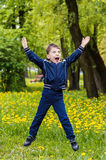 Smiling happy boy is jumping on green background. On green field Royalty Free Stock Images
