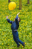 Smiling happy boy is jumping whith yellow balloon. Smiling happy boy is jumping on green background whith yellow balloon stock photo