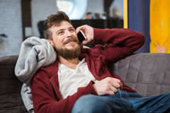 Smiling happy boy lying and talking on mobile phone Stock Photos