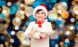 Smiling happy boy in santa hat with christmas gift. Holidays, christmas, childhood and people concept - smiling happy boy in santa hat with gift box over lights Royalty Free Stock Photos