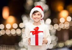 Smiling happy boy in santa hat with christmas gift. Holidays, presents, childhood and people concept - smiling happy boy in santa hat with gift box over Stock Photography