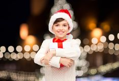 Smiling happy boy in santa hat with christmas gift. Holidays, presents, childhood and people concept - smiling happy boy in santa hat with gift box over Royalty Free Stock Photography