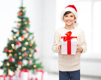 Smiling happy boy in santa hat with gift box Royalty Free Stock Photography