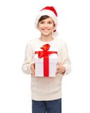 Smiling happy boy in santa hat with gift box. Holidays, presents, christmas, childhood and people concept - smiling happy boy in santa hat with gift box Royalty Free Stock Photo