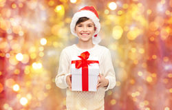 Smiling happy boy in santa hat with gift box. Holidays, presents, christmas, childhood and people concept - smiling happy boy in santa hat with gift box over Stock Images