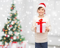 Smiling happy boy in santa hat with gift box. Winter holidays, childhood and people concept - smiling happy boy in santa hat with gift box over snow and Royalty Free Stock Photos