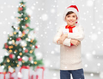 Smiling happy boy in santa hat with gift box. Winter holidays, childhood and people concept - smiling happy boy in santa hat with gift box over snow and Stock Images