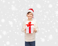 Smiling happy boy in santa hat with gift box. Winter holidays, presents, christmas, childhood and people concept - smiling happy boy in santa hat with gift box Stock Photo