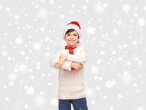 Smiling happy boy in santa hat with gift box. Winter holidays, presents, christmas, childhood and people concept - smiling happy boy in santa hat with gift box Royalty Free Stock Images
